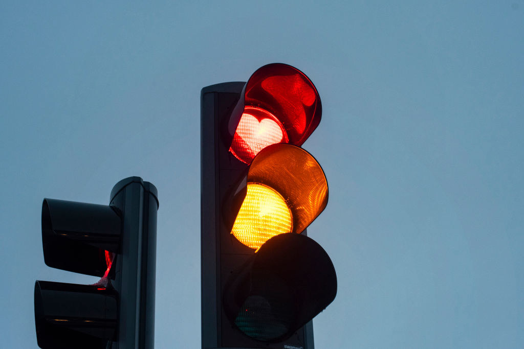 A stoplight against a blue sky with its yellow light and red light, the latter of which is shaped like a heart, lit up