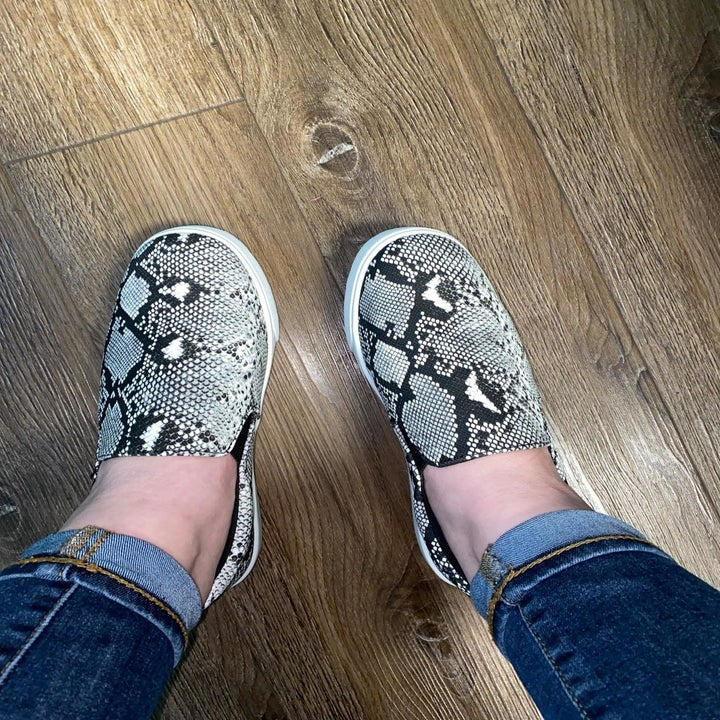 reviewer wears black and white faux snakeskin print shoes with jeans
