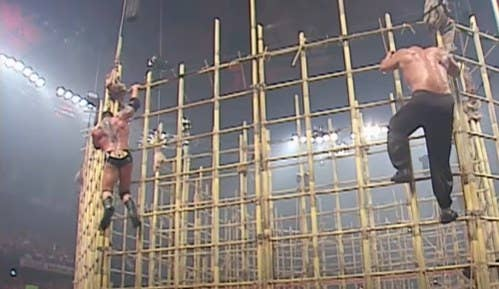 Two men climbing down a bamboo cage.