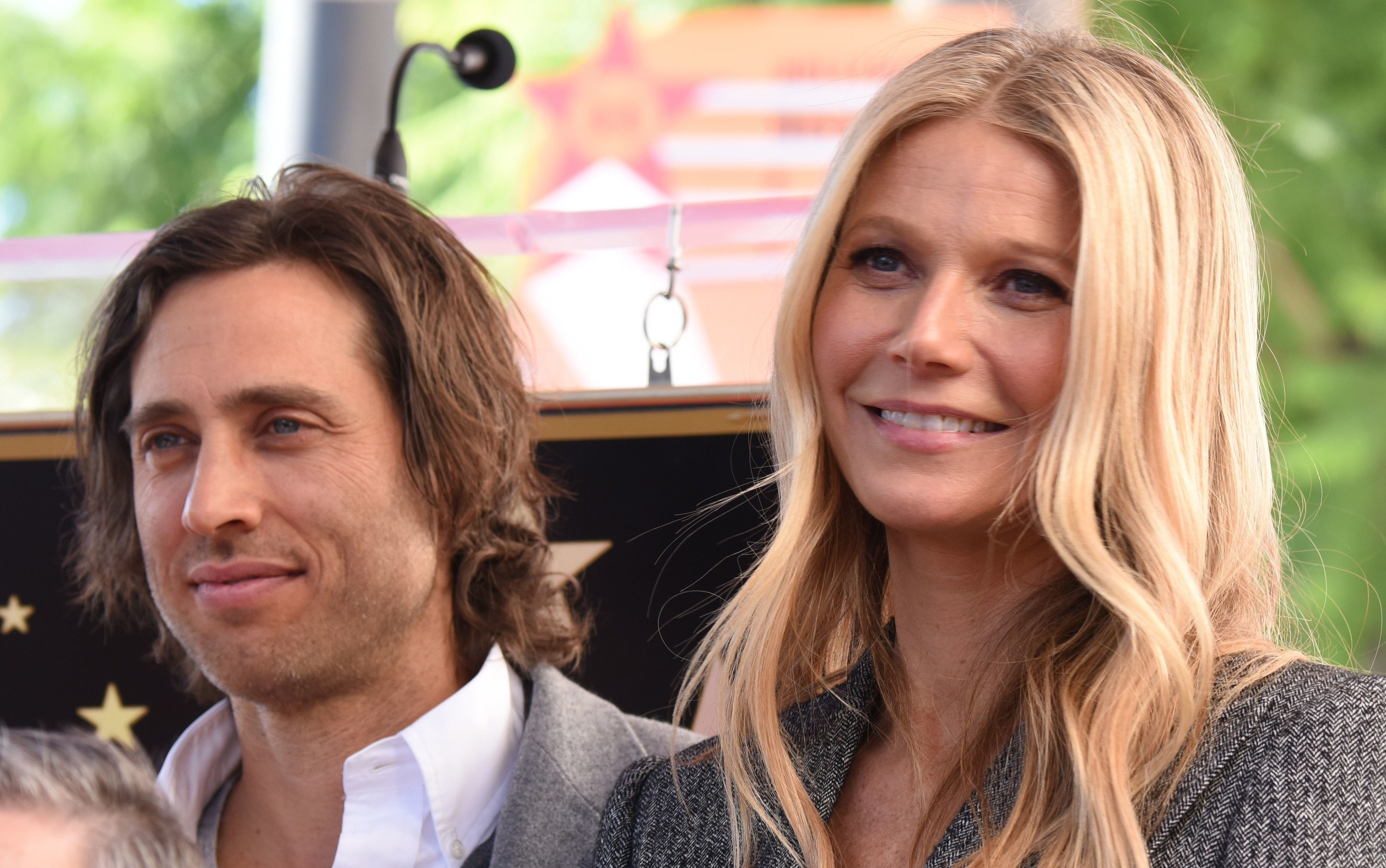 Gwyneth smiles while standing next to Brad at an event