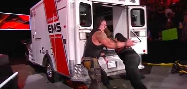 Man jumping into an ambulance while another man pretends to toss him inside.