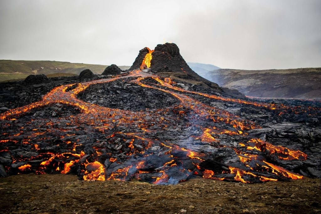 A volcano bubbled red-hot lava across an open field