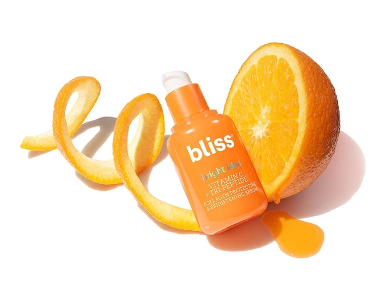 An orange serum bottle sitting on an orange peel