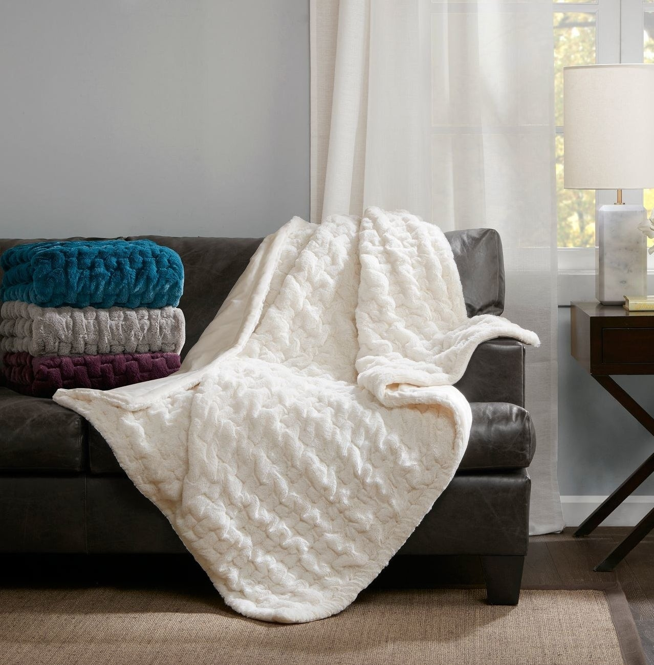 A white throw blanket spread over a couch