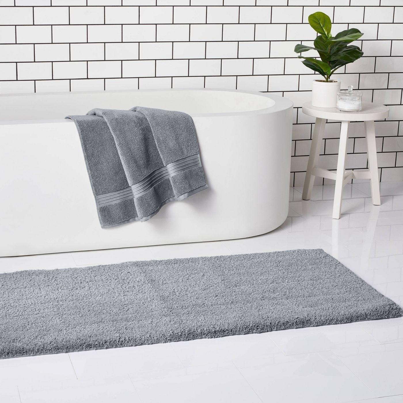 A grey bath rug in outside a bathtub