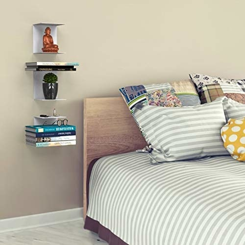 Bookshelf on the side of a bed.
