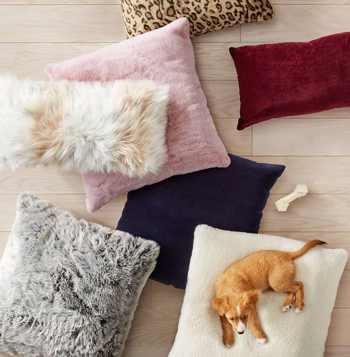 A pile of faux fur throw pillows on the ground with a dog