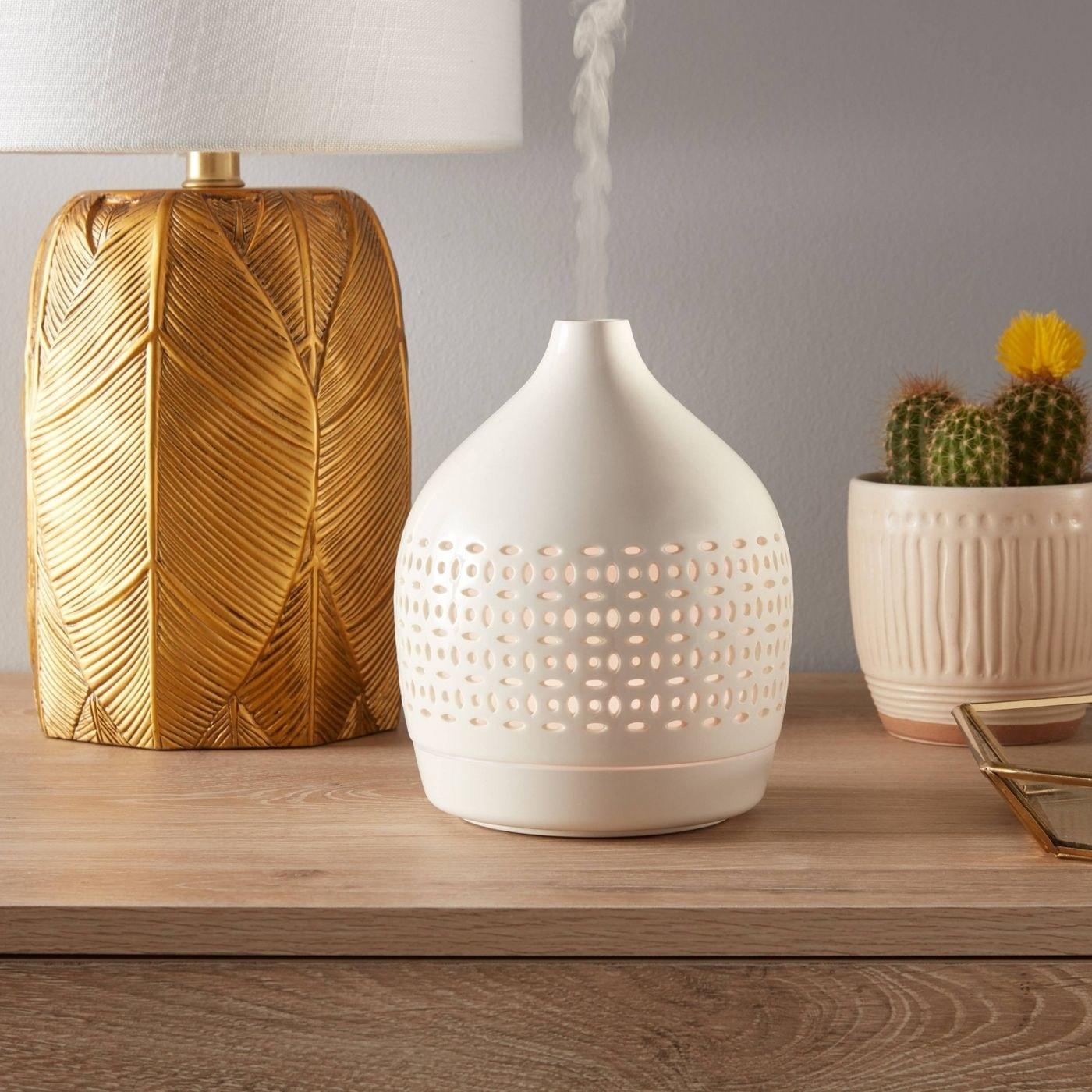 A white ceramic cutout diffuser on a console table