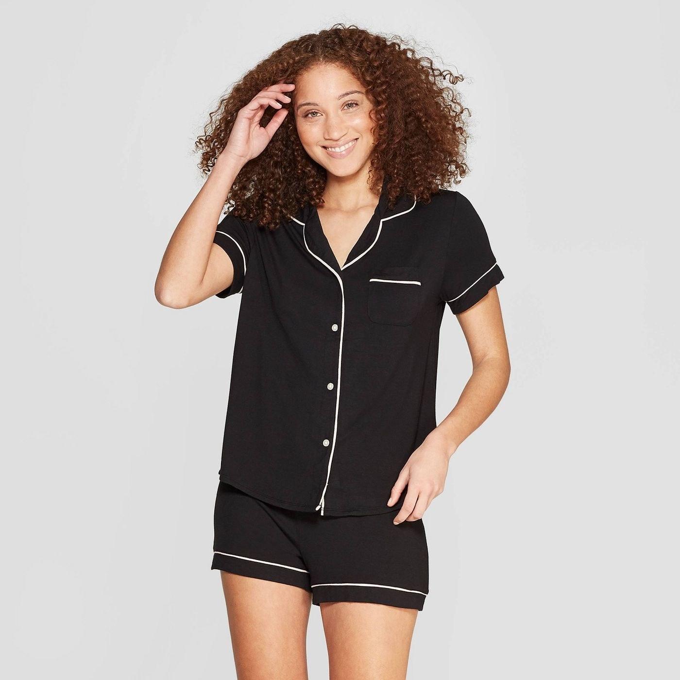 A model wearing a black button shirt and shorts pajama set