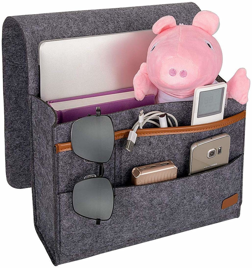Grey bedside caddy with a remote, phone, journal, power bank, toy, laptop, pair of sunglasses, and charging cables
