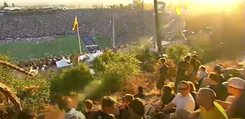 Students sitting on Tightwad Hill overlooking Cal's stadium.