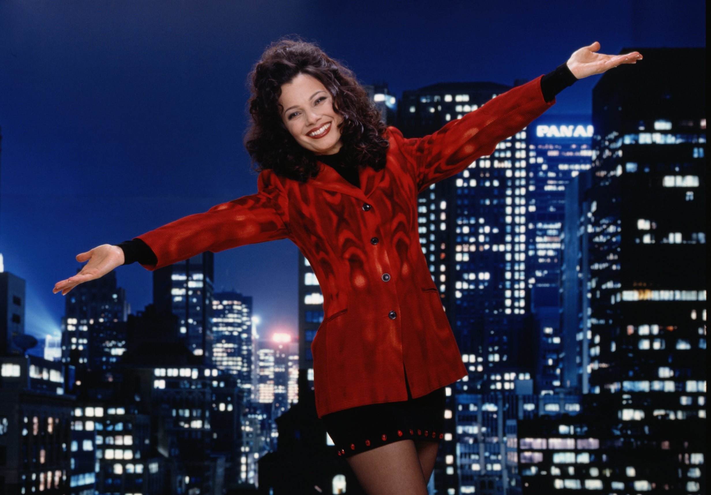 Fran holds her arms out wide in front of a New York City backdrop