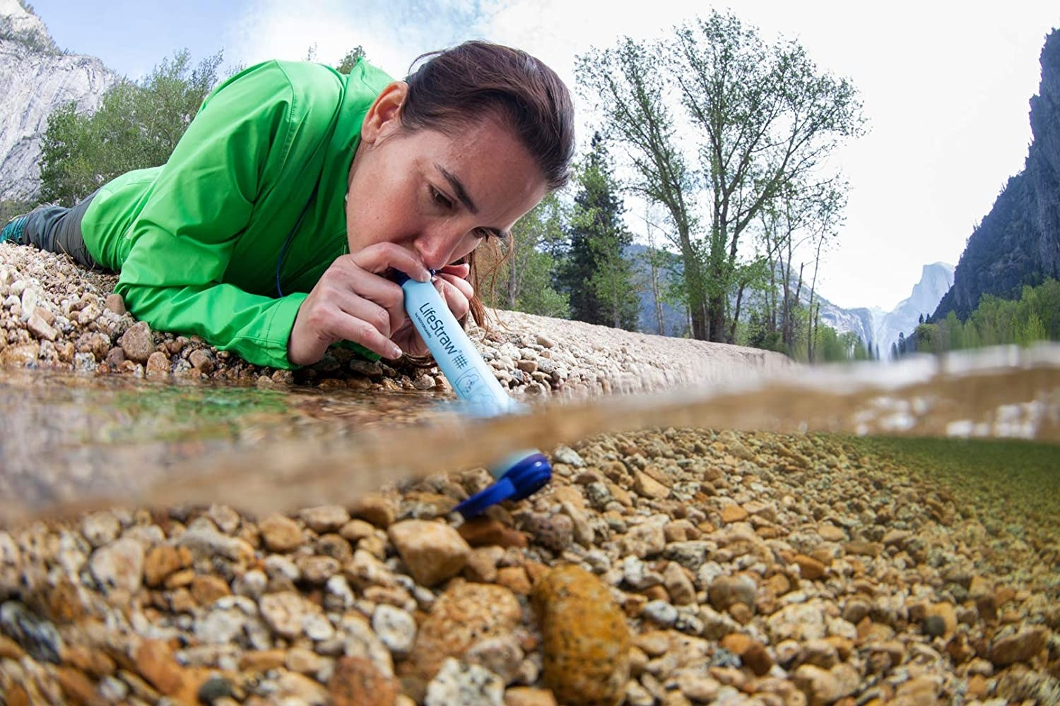 A person drinking river water out of the LifeStraw