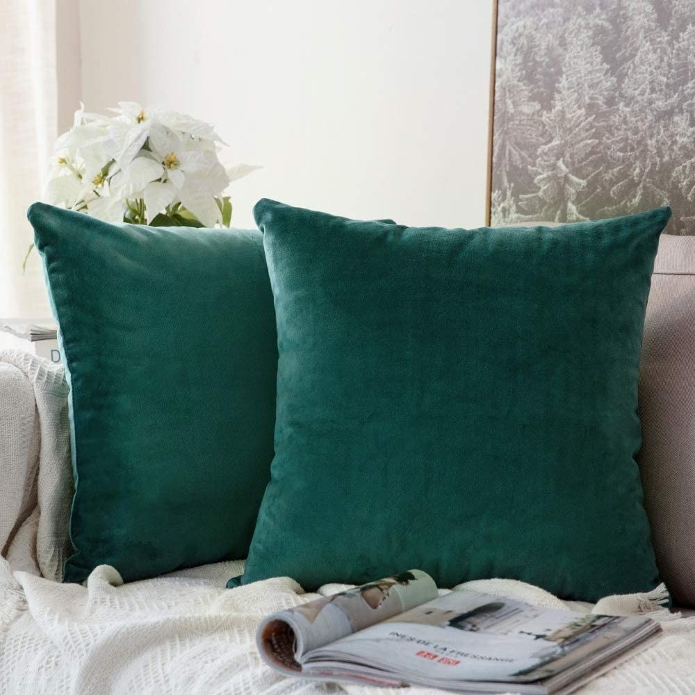 two green velvet throw pillows on a couch