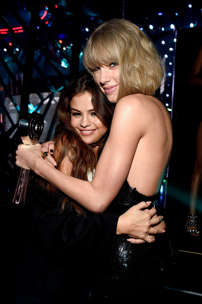 Taylor Swift (R) embraces actress/singer Selena Gomez backstage at the iHeartRadio Music Awards