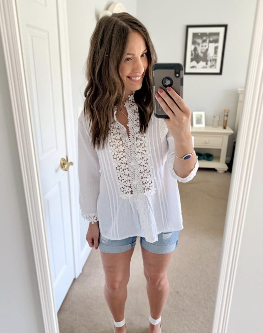 Person is wearing a white blouse with floral detail and denim shorts