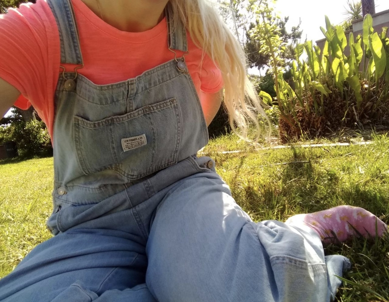 Person is wearing light denim overalls and a pink top