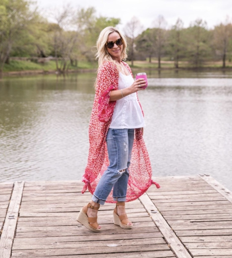 Person is wearing a white top, denim jeans, and a pink chiffon cardigan over it