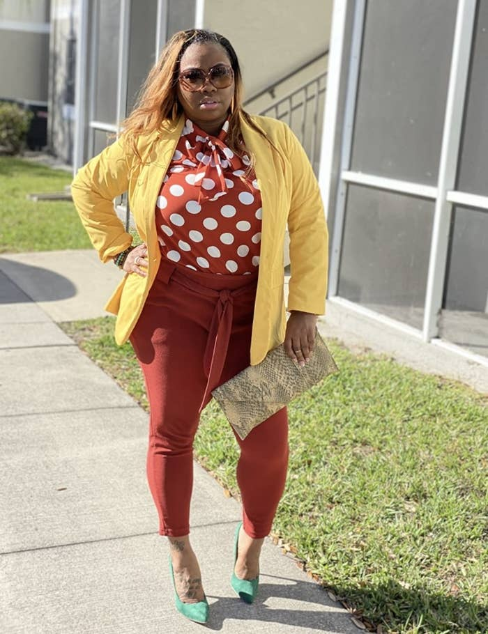Person is wearing red pants, a red polka dot top and yellow cardigan on top