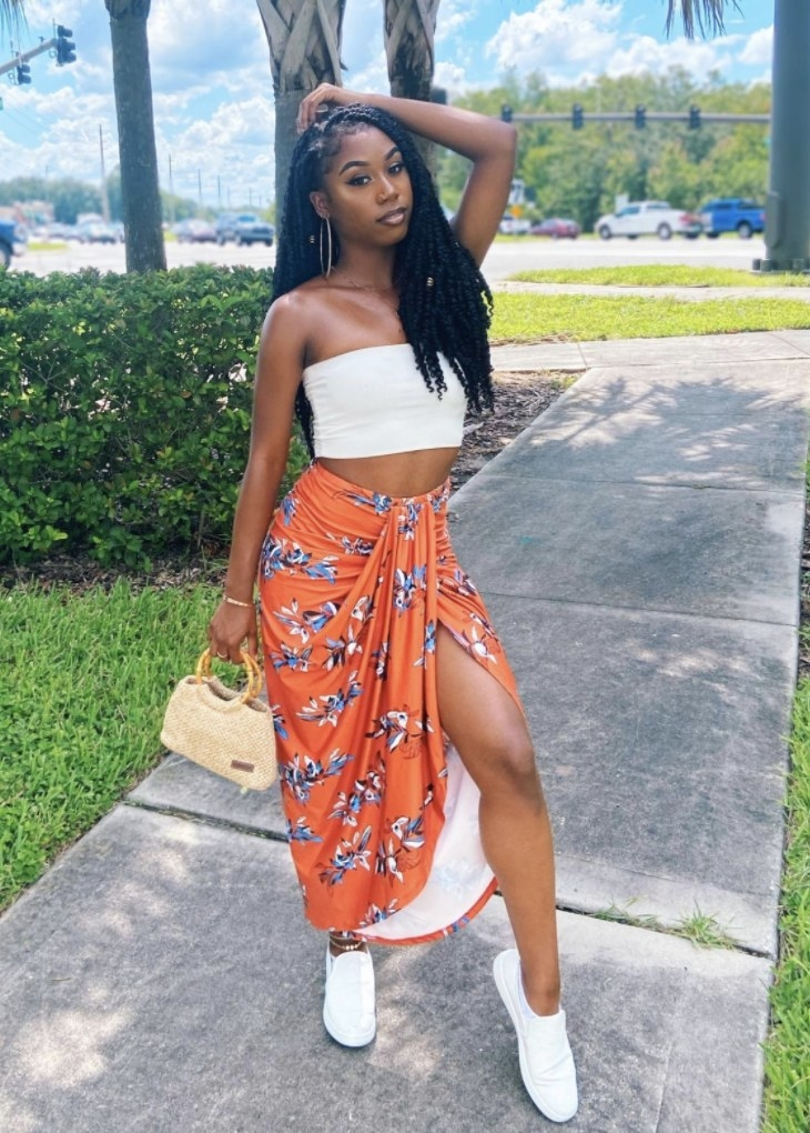 Person is wearing an orange skirt and white tube top