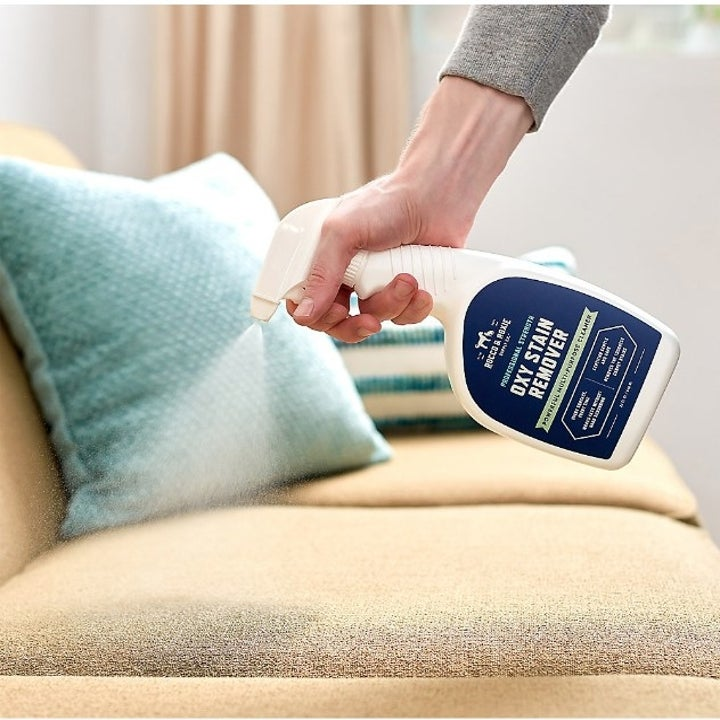 The stain remover being used on a couch