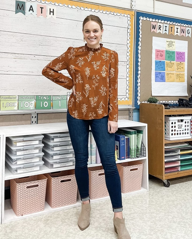Reviewer photo of a person wearing denim jeans and a burnt orange chiffon blouse