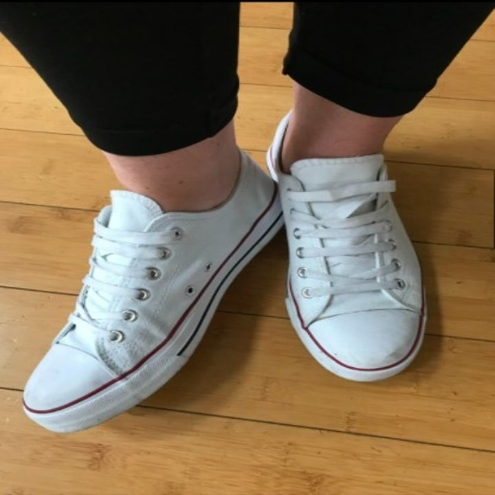 person wearing white canvas sneakers