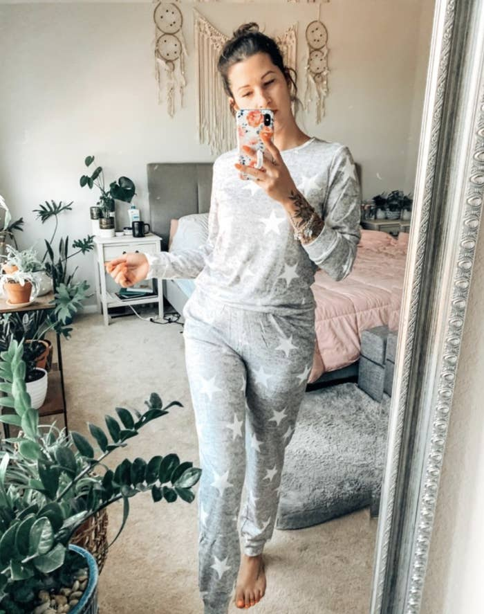 Person is wearing a grey pajama set with white stars all over it