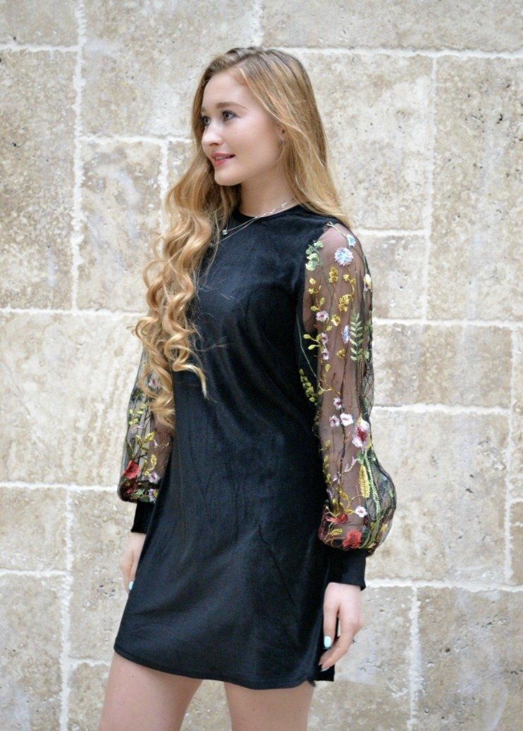 Person is wearing a black dress with mesh sleeves that have floral details on them
