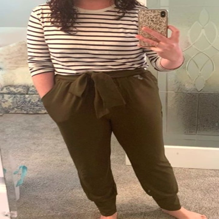person wearing army green paper bag pants and a striped t shirt