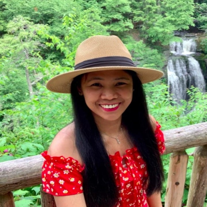 person wearing a straw wide brim hat with a cute red top