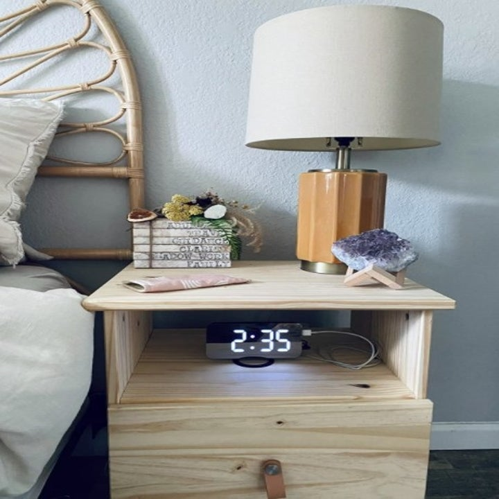 a bed side table with a digital alarm clock on it