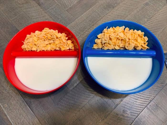 two cereal bowls with cereal on one side and milk on the other