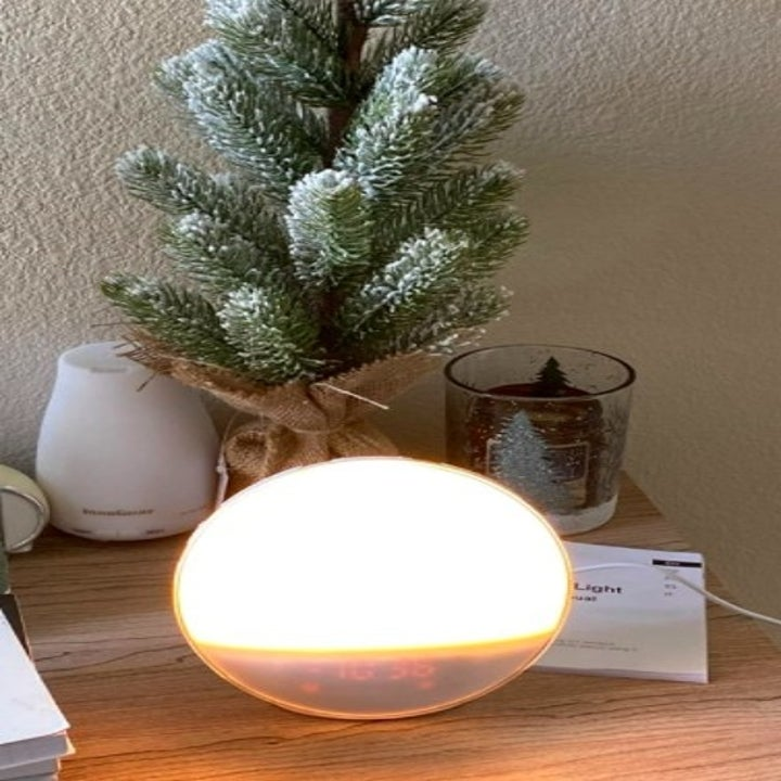 a digital alarm with a natural glow that's sitting on a bedside table