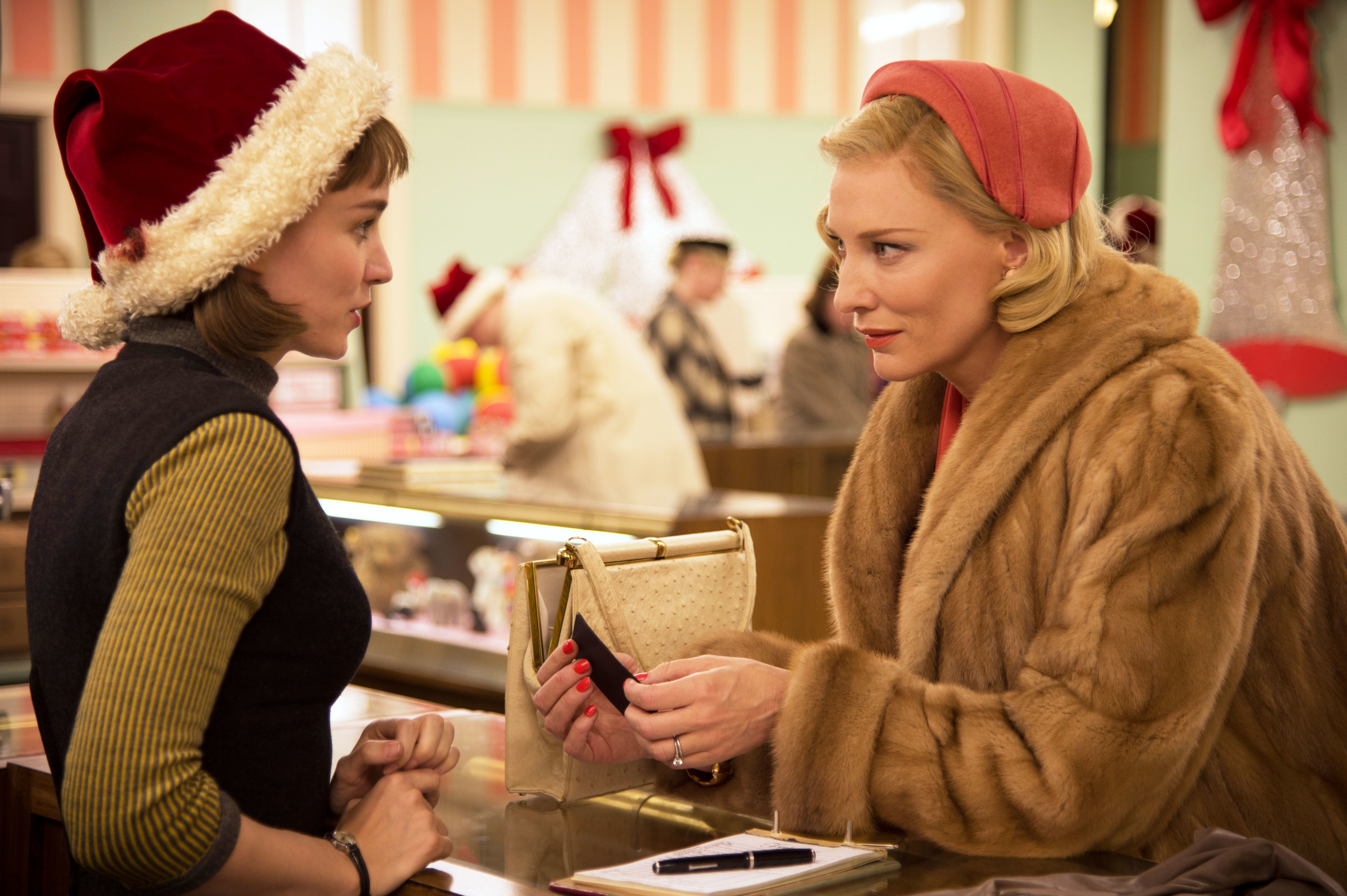 Rooney Mara and Cate Blanchett talking to one another in a department store in a scene from Carol