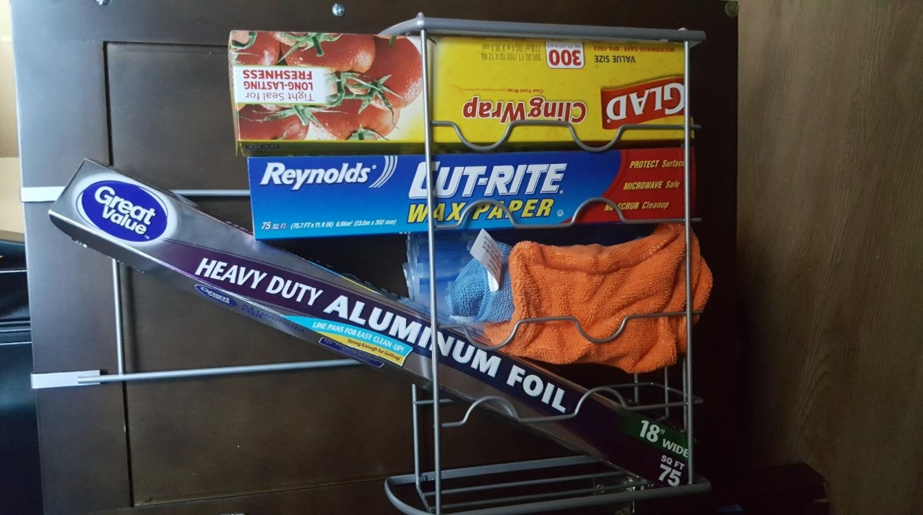 The reviewer's photo of the over the door storage organizer holding trash bags and foil