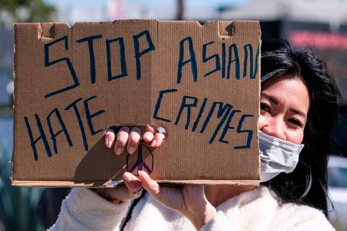 """Woman holding up a sign that says """"Stop Asian hate crimes"""""""