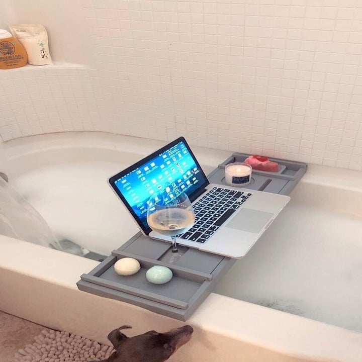 the bathtub caddy over a bubble bath with a wine glass and laptop on it