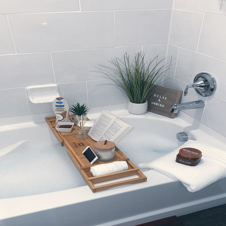 a bathtub caddy over a bubble bath with a book, phone, and other items on it