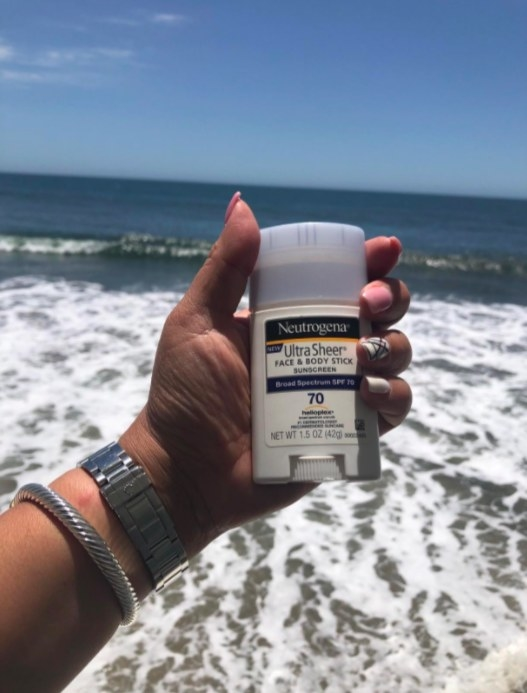 person holding up a stick of neutrogena face and body sunscreen