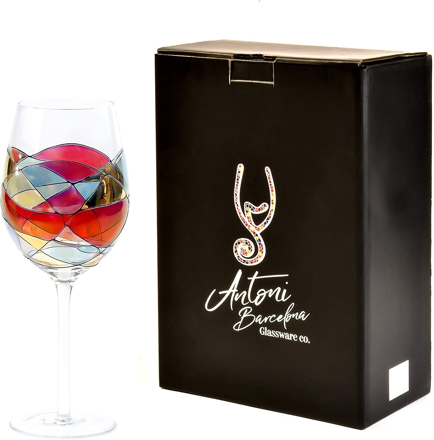 one antoni barcelona painted wine glass next to its box packaging