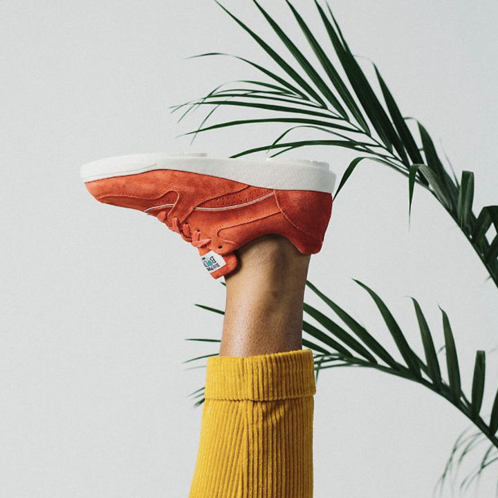 flexed foot with same style sneaker in a copper/red shade