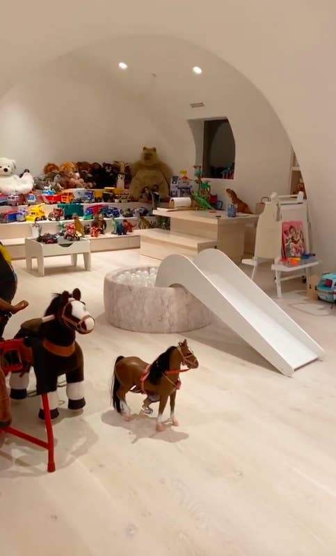 A neutral toned room filled with toys like mini rocking horses and stuffed animals