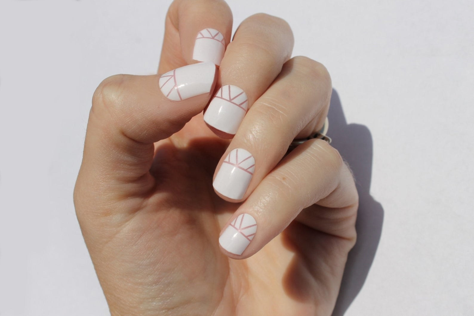 Model with white patterned nail wraps