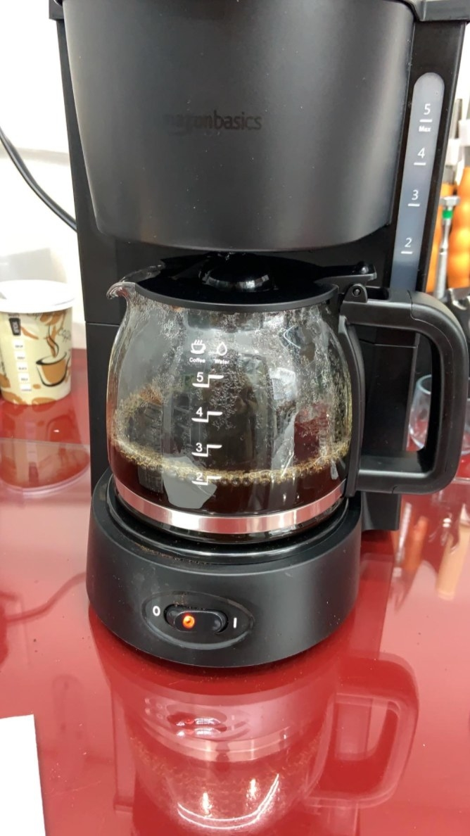 The reviewer's photo of the coffee machine brewing a pot of coffee