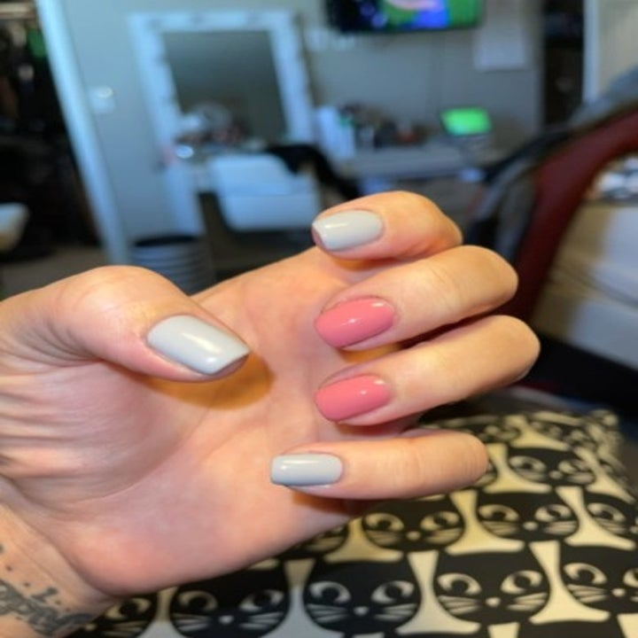 person with a pink and gray at home manicure