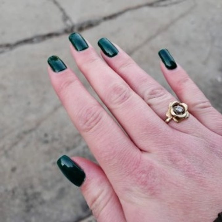 person with dark green at home manicure