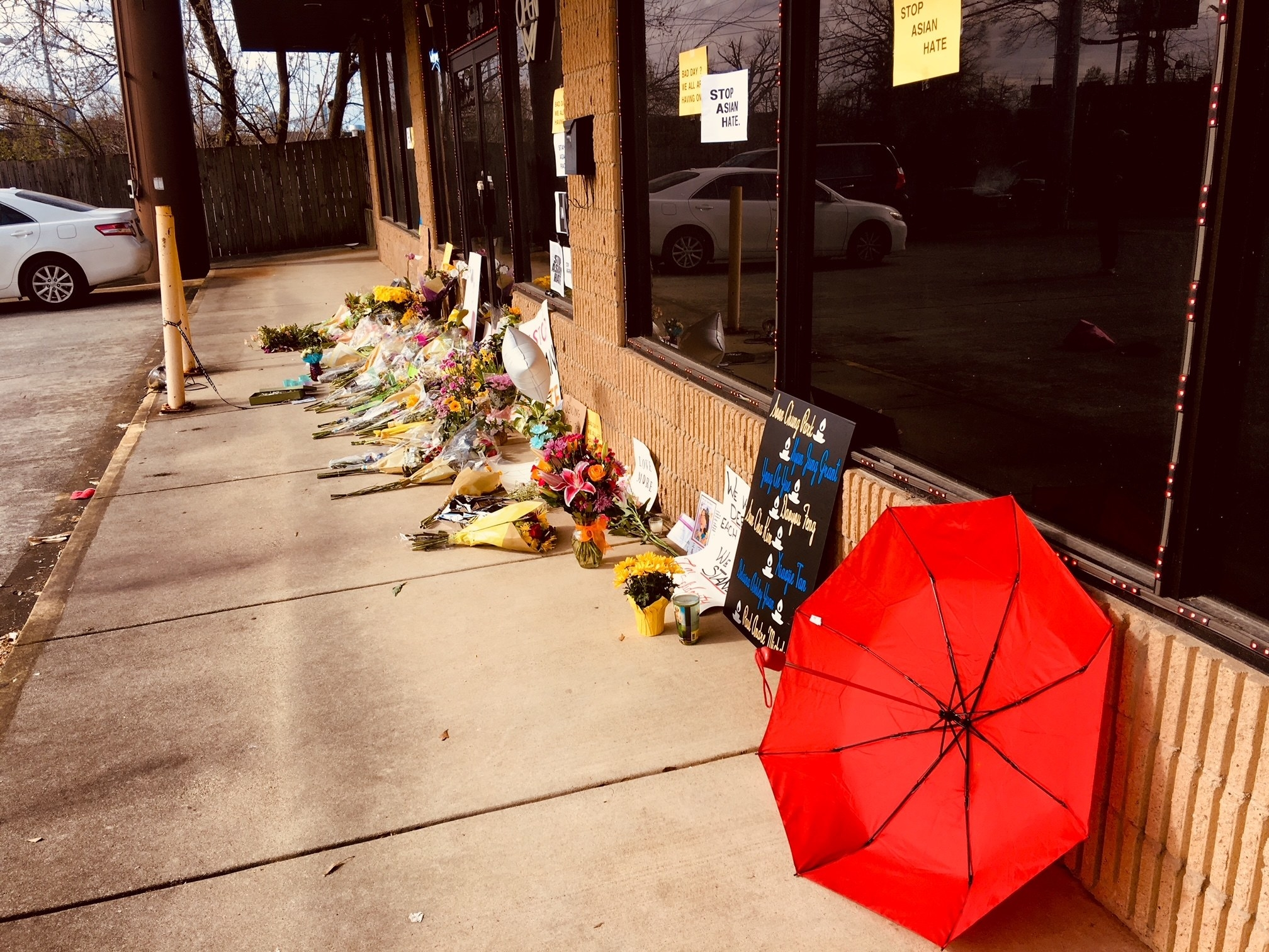 A red umbrella and memorials outside a storefront