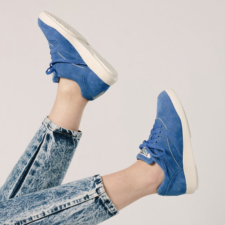 model in blue lace-up sneakers and acid wash denim