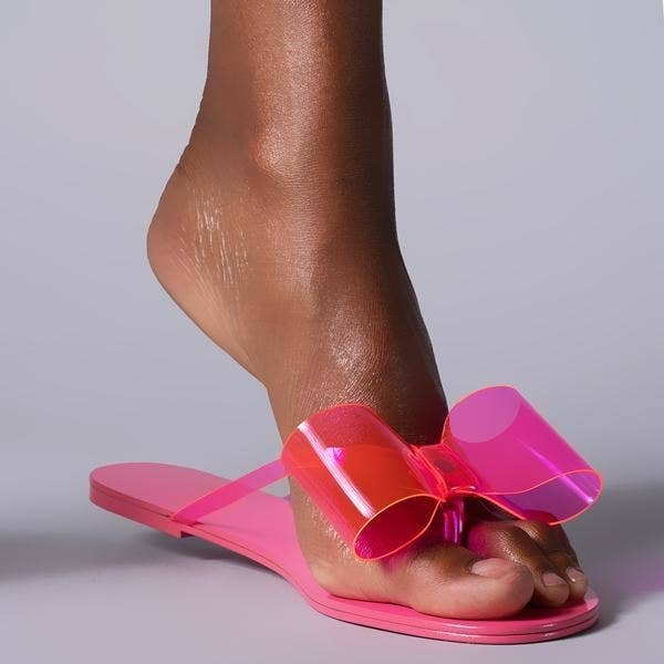 model wears pink jelly material flip-flops with bow detailing